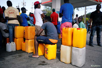 People stand in line waiting to buy fuel, in Port-au-Prince, Haiti, Feb. 13, 2019.