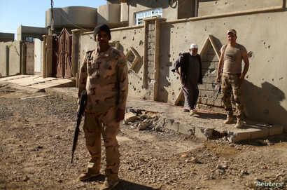 Iraqi soldiers stand guard in Al-Shayma neighborhood that was captured by Iraqi forces from Islamic State militants, southeast of Mosul, Iraq, Nov. 22, 2016. The IS reportedly has used chemical weapons during 19 attacks in areas around Mosul.