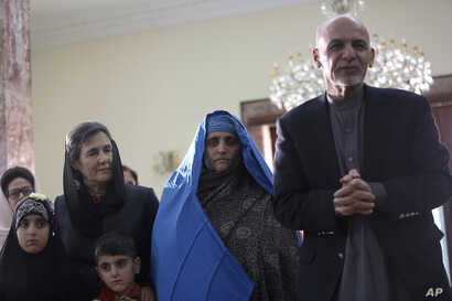 "Afghan President Ashraf Ghani, right, meets with National Geographic's famed green-eyed ""Afghan Girl"" Sharbat Gulla at the Presidential palace in Kabul, Afghanistan, Nov. 9, 2016."