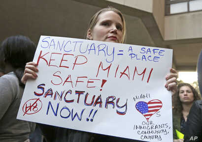 Protester Jennifer Smith-Camejo holds a sign during an anti-Trump and anti-Gimenez rally in downtown Miami, Jan. 31, 2017. Miami-Dade County Mayor Carlos Gimenez had issued a controversial order assuring the Trump administration that Miami-Dade was n