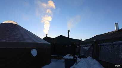 """""""Chimneys"""" fume in the camp from wood stove heaters set up in long-term tents. (E. Sarai/VOA)"""
