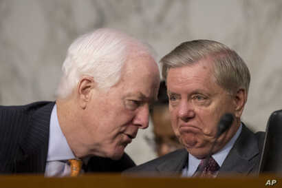 Senate Majority Whip  John Cornyn, R-Texas., left, speaks with Sen. Lindsey Graham, R-S.C., right, during a Senate Judiciary Committee hearing on Capitol Hill in Washington, Oct. 3, 2017, on the Trump administration's decision to end Deferred Action ...