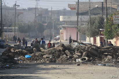 Streets around military bases near the front lines in Mosul are baracaded with piles of dirt and old vehicles to prevent car bombs from approaching in Mosul, Iraq, Jan. 11, 2017.