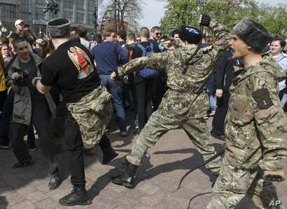 Fighters of National Liberation movement clash with protesters during clashes at a demonstration against President Vladimir Putin in Pushkin Square in Moscow, Russia, May 5, 2018.