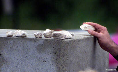 FILE - A member of the family of one of the victims places a stone on top of the monument at Jedwabne, Poland, July 10, 2001. During the German Nazi occupation of Poland, Poles killed at least 340 Jews at the site on July 10, 1941. Most of the victim...