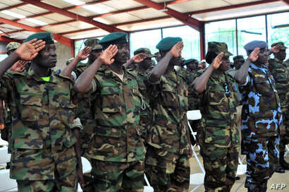 FILE – Members of the Uganda People's Defense Forces (UPDF) salute after completing a nine-week course led by Marines of the Special Purpose Marine Air-Ground Task Force (SPMAGTF) at a training center in Singo, Sept. 28, 2013.