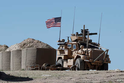 FILE - In this April 4, 2018 file photo, a U.S. soldier sits on an armored vehicle at a newly installed position, near the tense front line between the U.S-backed Syrian Manbij Military Council and the Turkish-backed fighters, in Manbij, north Syria....