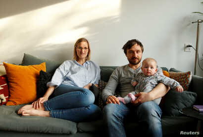 FILE - Lucie Sol, 32, a social worker, her boyfriend, Rudie Jonkmans, 34, a cook, and their 22-week-old baby Lena Amelie pose for a photograph inside their house on the first day Lucie went back to work, in Purmerend, the Netherlands, Feb. 18, 2019. ...