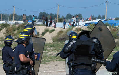 """French riot police stand guard at the entrance to """"the Jungle"""" as dozens of migrants try to storm trucks that are heading toward the ferry terminal in Calais, France, Sept. 21, 2016."""