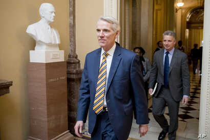 Sen. Rob Portman, R-Ohio, center, walks to a meeting with Republican Senate leadership at the offices of Senate Majority Leader Mitch McConnell of Ky. on Capitol Hill, Feb. 11, 2019, in Washington.