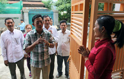 Newly elected commune chief from the opposition Cambodia National Rescue Party (CNRP) Sar Neang (2nd L) visits people in his commune, on the outskirts of Phnom Penh, Cambodia, June 8, 2017.