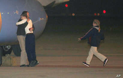 Jeffrey Fowle is greeted by his son and other family members upon his arrival, early Wednesday, Oct. 22, 2014, at Wright-Patterson Air Force Base, Ohio.
