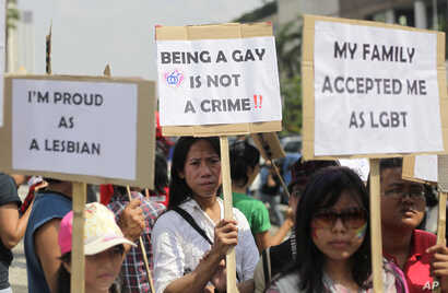 FILE - Indonesian gay activists hold posters during a protest demanding equality for LGBT (Lesbian, gay, bisexual and transgender) people in Jakarta, Indonesia, May 21, 2011.