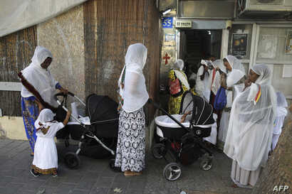 FILE - Christian African Eritrean migrants gather ahead of praying at a makeshift church in southern Tel Aviv on Sept. 2, 2017.