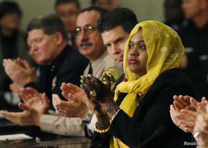 FILE - Deeqo Jibril (right) applauds United States Vice President Joe Biden after Biden's opening remarks at a roundtable on countering violent extremism at the White House in Washington, Feb. 17, 2015.