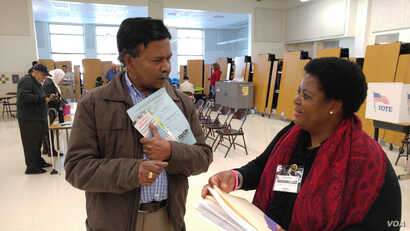Virginia voter gets election materials from polling station worker before voting in US presidential election, Nov. 8, 2016. (Photo: D. Block / VOA)