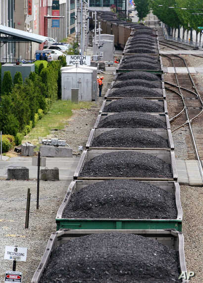 FILE - A train hauling coal runs between office buildings, condos and the downtown waterfront in Seattle, Wash. Scientific consensus holds that the emission of greenhousegases from the burning of fossil fuels is the main cause ofglobal warming.