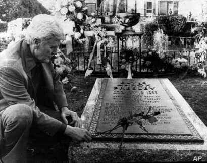 Vernon Presley, Elvis Presley's father, places a rose on his son's grave Nov. 24, 1977 as newspeople were permitted inside the grounds at Graceland in Memphis, Tenn. for the first time since Elvis' funeral.