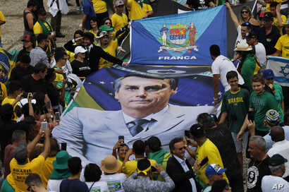 People hold a banner with a photo of Brazil's former army captain Jair Bolsonaro before the swearing-in ceremony, in front of the Planalto palace in Brasilia, Jan. 1, 2019.