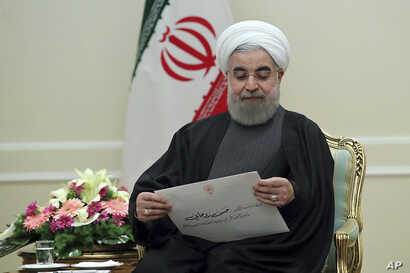 President Hassan Rouhani holds a letter from Gulf Arab nations, given to him by Kuwait's Foreign Minister Sabah Khaled al-Sabah, Jan. 25, 2017.