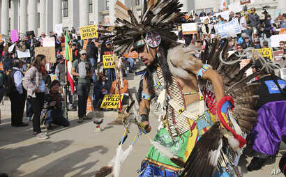A supporter of the Bears Ears and Grand Staircase-Escalante National Monuments dances with a headdress during a rally Saturday, Dec. 2, 2017, in Salt Lake City.