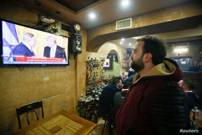 A Palestinian man watches a joint press conference by U.S. President Donald Trump and Israeli Prime Minister Benjamin Netanyahu, in a coffee shop in the West Bank city of Hebron, Feb. 15, 2017.