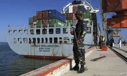 A Pakistan Navy soldier stands guard while a loaded Chinese ship is readied for departure at Gwadar port, Nov. 13, 2016.