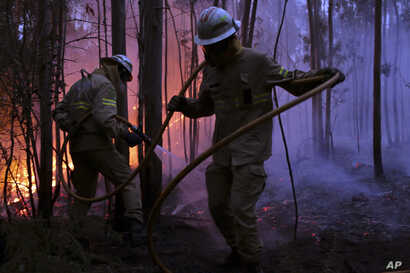 Portuguese National Republican Guard firefighters work to stop a forest fire from reaching the village of Avelar, central Portugal, June 18 2017. A number of people have been killed in forest fires in central Portugal, many of them trapped in their c...