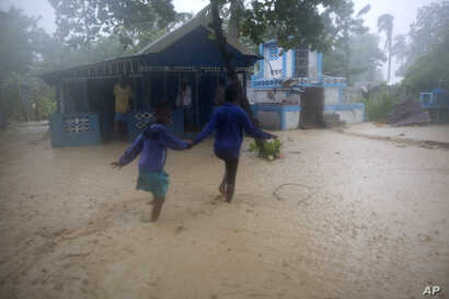 Residents wade through flood waters in Leogane, Haiti, Oct. 4, 2016