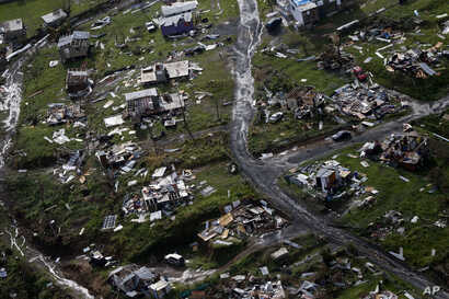 FILE - Destroyed communities are seen in the aftermath of Hurricane Maria in Toa Alta, Puerto Rico, Sept. 28, 2017. Puerto Rico's governor demanded action from U.S. Congress after announcing Feb. 27, 2018, that the Treasury Department has cut a nearl...