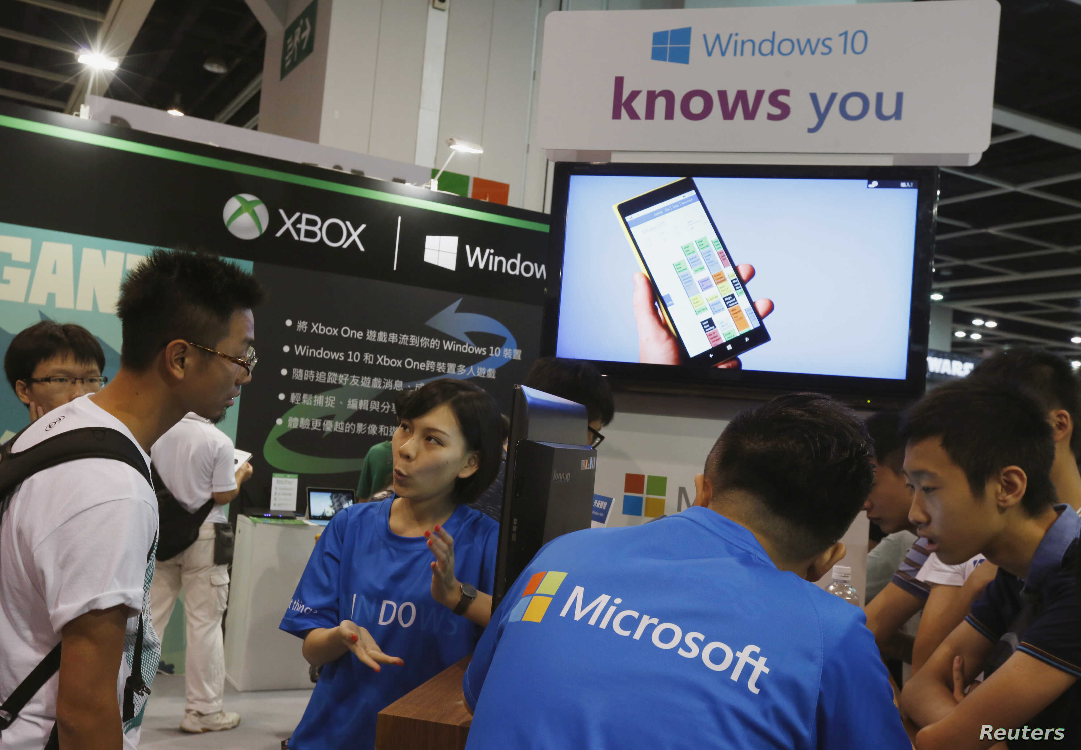 FILE - Promotional staff talk to gamers at the Microsoft Windows 10 booth at Ani-Com & Games Hong Kong in Hong Kong, China.