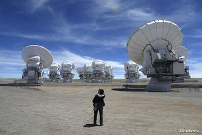FILE - A member of the media takes pictures of the parabolic antennas of the ALMA (Atacama Large Millimetre/Submillimetre Array) project at the El Llano de Chajnantor in the Atacama desert, some 1,730 km (1,074 miles) north of Santiago and 5,000 mete...