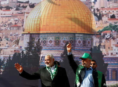 Hamas Chief Ismail Haniyeh and Gaza's Hamas Chief Yehya Al-Sinwar gesture to supporters during a rally marking the 30th anniversary of Hamas' founding, in Gaza City, Dec. 14, 2017.