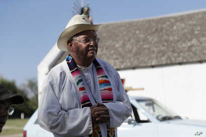 In this Aug. 12, 2017, photo, Father Roy Snipes is shown after he led a procession to the La Lomita Chapel along a levee toward the Rio Grande to oppose the wall the U.S. government wants to build on the river separating Texas and Mexico in Mission, ...
