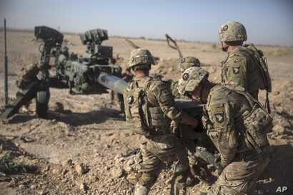 FILE - U.S. soldiers ready a howitzer to be towed into position at Bost Airfield in Afghanistan's Helmand Province in this June 10, 2017 photo provided by Operation Resolute Support.