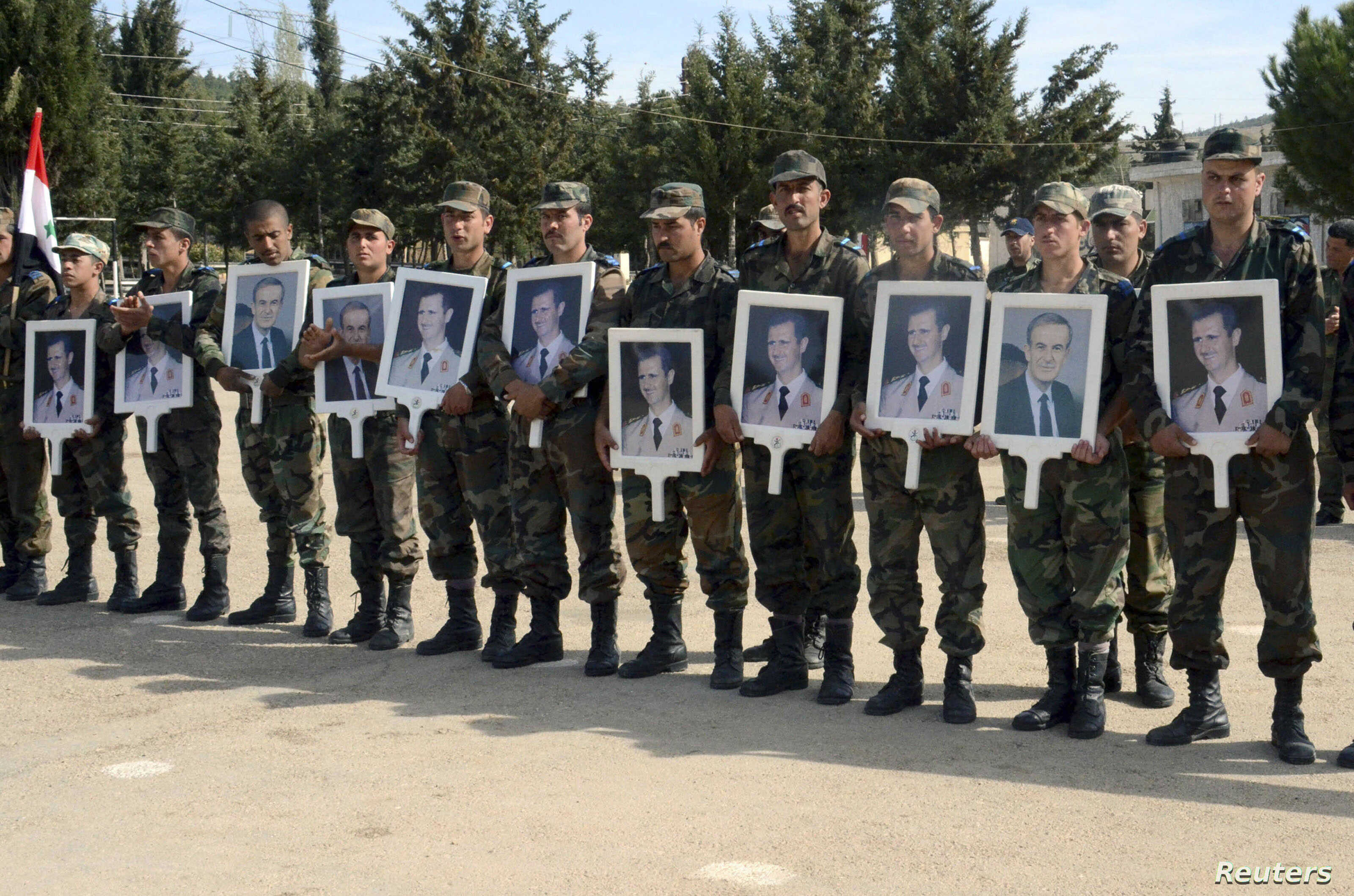 Forces loyal to Syria's President Bashar al-Assad carry pictures of him and his late father, former Syrian president Hafez al-Assad, as they commemorate the 67th anniversary of the founding of the Baath party, at an undisclosed location, in this hand...