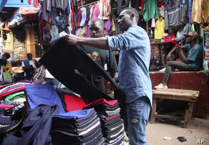 A man looks at second hand trousers at a market in Kampala, Uganda, April 6, 2018. The used clothes cast off by Americans and sold in bulk in African nations have been blamed in part for undermining local textile industries.