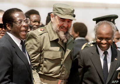 FILE - This photo taken on Aug. 31, 1986 shows Cuban President Fidel Castro (C), flanked by Zimbabwean President Robert Mugabe (L), as he arrives in Harare, for the 8th non-aligned summit in Zimbabwe.