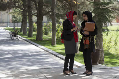 Female Afghan journalist, right, speaks with Adela Raz, deputy spokesperson to former Afghan President Hamid Karzai as they await a joint press conference by U.S. Secretary of State John Kerry and then-President Karzai at the Presidential Palace, Kab...