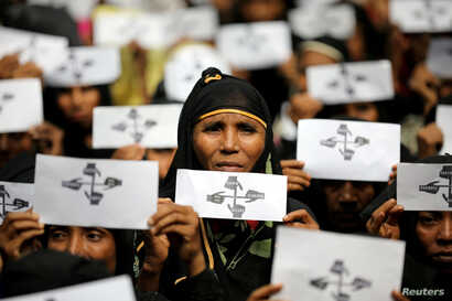 FILE - Rohingya refugee women hold placards as they take part in a protest at the Kutupalong refugee camp to mark the one-year anniversary of their exodus, in Cox's Bazar, Bangladesh, Aug. 25, 2018.