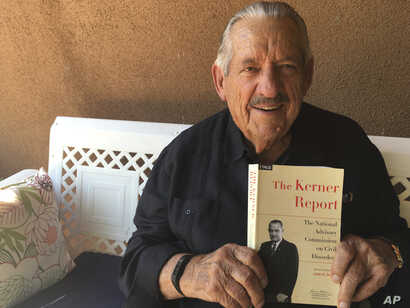 FILE - Former U.S. Sen. Fred Harris of Oklahoma holds a copy of the Kerner Report at his home in Corrales, N.M., Aug. 31, 2017.