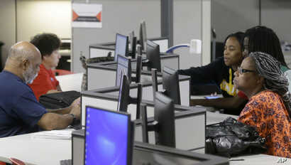 FILE - Jobseekers use computers to search for a job at the Texas Workforce Solutions office in Dallas, March 10, 2017.