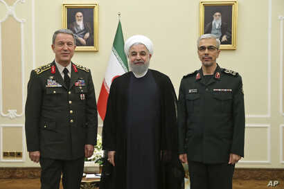 In this photo released by an official website of the office of the Iranian Presidency, President Hassan Rouhani, center, poses for a photo with Turkey's Chief of Staff Gen. Hulusi Akar, left, and Chief of Staff of Iran's Armed Forces, Gen. Mohammad H...