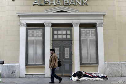 A man walks past a bank next a homeless sleeping on the pavement in central Athens, Greece, Feb. 28, 2017.