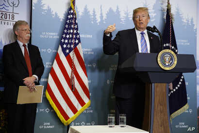 National Security Adviser John Bolton looks on as President Donald Trump speaks during a news conference at the G-7 summit,  June 9, 2018, in La Malbaie, Quebec, Canada.