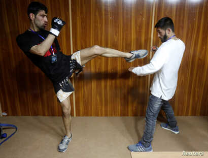 Fighters and team members prepare backstage before matches of a mixed martial arts competition in Kabul, Afghanistan, March 30, 2017.