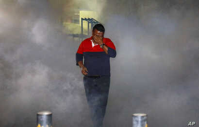 A Maldivian opposition protester demanding the release of political prisoners is engulfed in tear gas fired by police during a protest in Male, Maldives, Feb. 2, 2018.