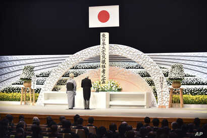 Japanese Emperor Akihito, right, along with Empress Michiko, delivers a speech in front of an altar for the victims of the March 11, 2011 earthquake and tsunami at the national memorial service in Tokyo Friday, March 11, 2016.