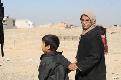 In the suburbs of Mosul, women seek food and medical care near army outposts.  They say along with cruel indignities, Islamic State militants also brought with them wide scale extreme poverty on Nov. 19, 2016. (Photo: H.Murdock/VOA)