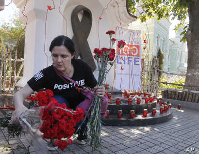 A woman lays flowers at the memorial monument dedicated to AIDS victims to mark the World Memory Day of people who died of AIDS in Kiev, Ukraine, May 19, 2017.